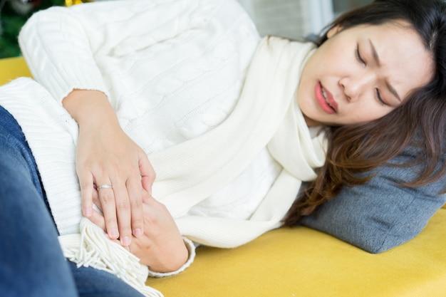 La copertura asiatica della donna per alleviare il dolore allo stomaco dopo aver avuto il ciclo mestruale Foto Premium