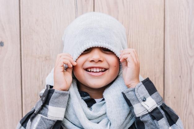 La copertura del ragazzino osserva con la protezione di inverno Foto Gratuite
