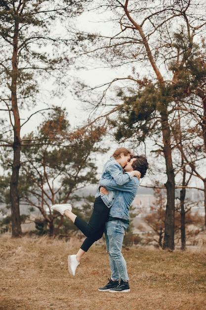 La coppia delicata ed elegante sta facendo una passeggiata nel parco di autunno Foto Gratuite
