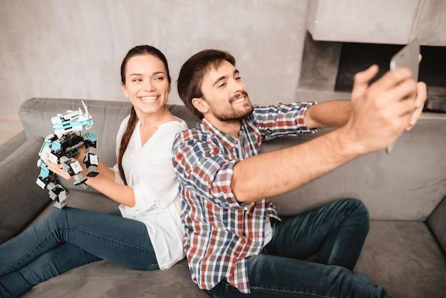 La coppia è seduta sul divano e fa selfie con robot. Foto Premium