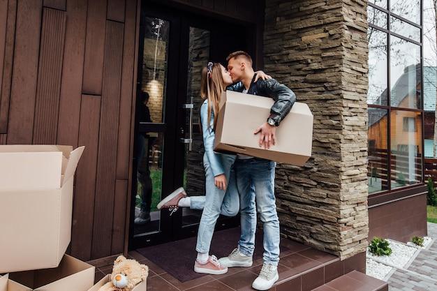 La coppia felice sta baciando con le scatole di cartone in nuova casa al giorno commovente. Foto Premium