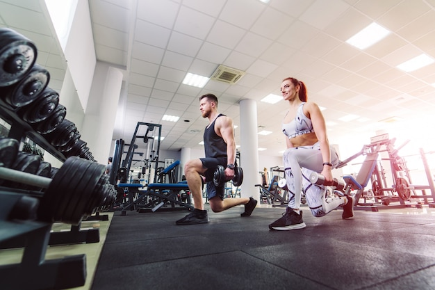 La coppia in buona salute nello sport copre il sollevamento delle teste di legno nella palestra. donna attraente e uomo bello che fanno allenamento con le teste di legno che stanno nella posa speciale nella società polisportiva. Foto Premium