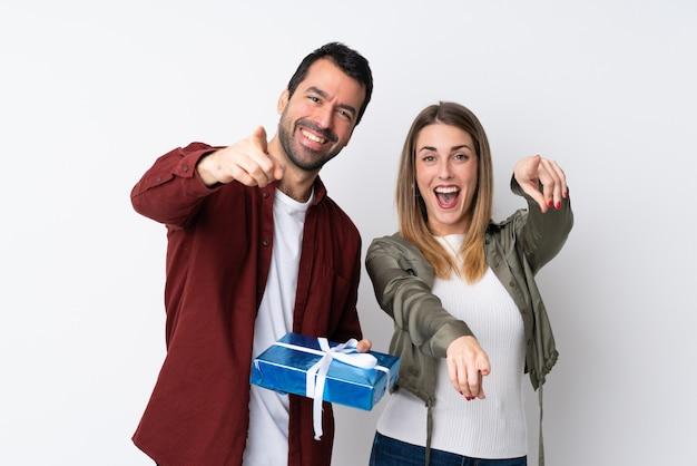 La coppia nel giorno di s. valentino che tiene un regalo sopra la parete isolata indica il dito voi con un'espressione sicura Foto Premium