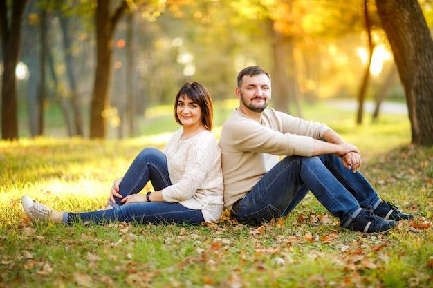 La coppia nell'amore si siede sulle foglie cadute in parco Foto Premium