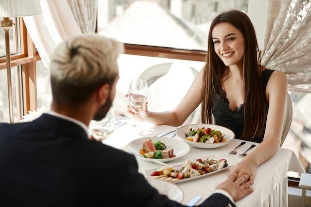 La coppia sta bevendo vino bianco durante la cena romantica al ristorante e si tiene per mano Foto Gratuite