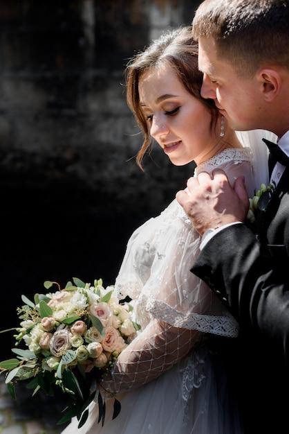 La coppia tenera di nozze sta abbracciando, ritratto dello sposo e sposa all'aperto con il mazzo di nozze, concetto di matrimonio Foto Gratuite