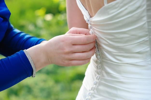 La damigella d'onore sta aiutando la sposa a vestirsi nel giorno del matrimonio Foto Premium