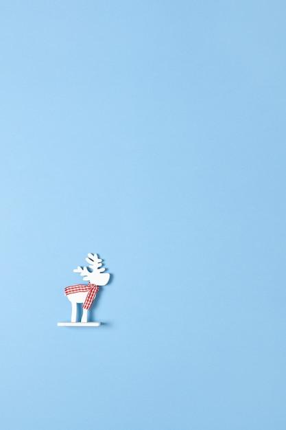 La decorazione di natale, gioca i cervi bianchi in sciarpa a quadretti su priorità bassa blu pastello con copyspace. festivo, capodanno. Foto Premium