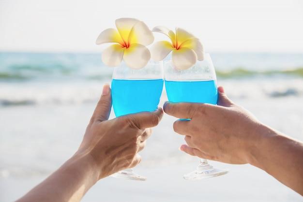 La decorazione di vetro di cocktail asiatico della tenuta di ccouple con la plumeria fiorisce con la spiaggia del mare dell'onda - felice rilassi la vacanza della celebrazione nel concetto della natura del mare Foto Gratuite