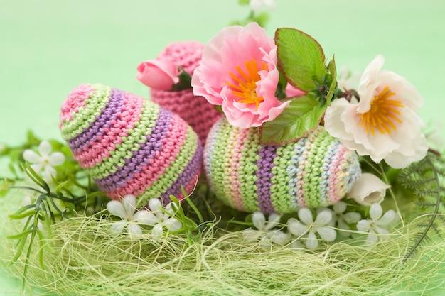 La decorazione tricottata di pasqua eggs, fiori su un fondo verde, fatto a mano Foto Premium
