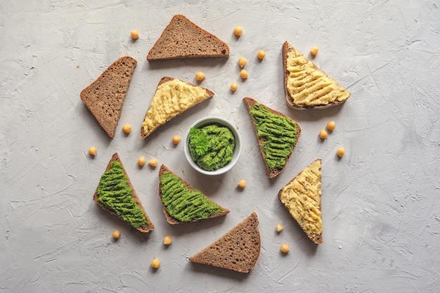 La diffusione sul pane di ceci. varie salse dip sul tavolo grigio, vista dall'alto Foto Premium