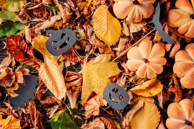La disposizione delle foglie di autunno mette con la vista superiore delle decorazioni di halloween Foto Premium