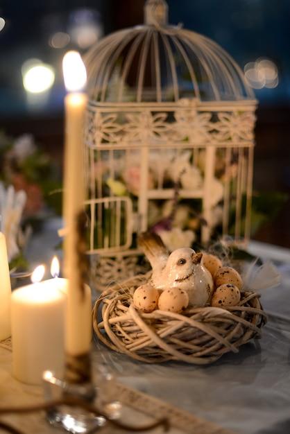 La disposizione floreale nella decorazione di nozze della gabbia un mazzo fiorisce con un uccello e un nido Foto Premium