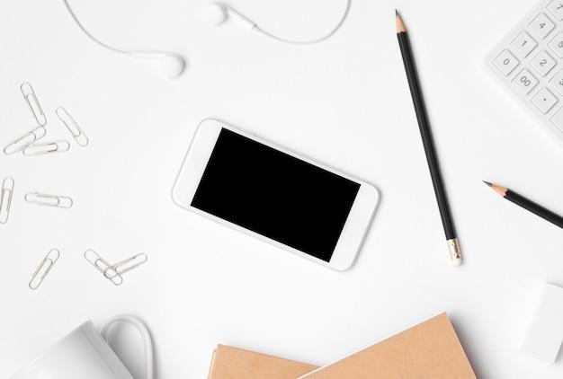La disposizione piana degli accessori dell'ufficio e l'esposizione in bianco dello smartphone sull'ufficio dello scrittorio Foto Premium