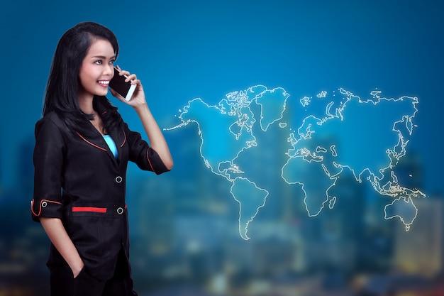 La donna abbastanza asiatica di affari parla sul telefono con il cliente di affari Foto Premium