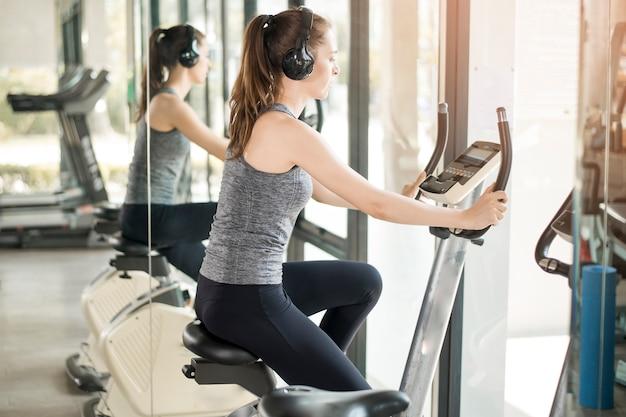 La donna abbastanza giovane di sport è esercizio sulla bicicletta in palestra Foto Premium