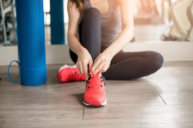 La donna abbastanza giovane di sport sta legando le sue scarpe da tennis in palestra, stile di vita sano Foto Premium