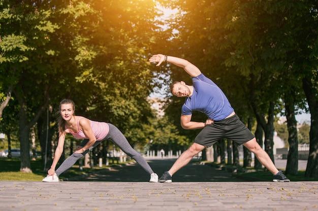 La donna adatta e l'uomo di forma fisica che fanno l'allungamento si esercitano all'aperto al parco Foto Gratuite