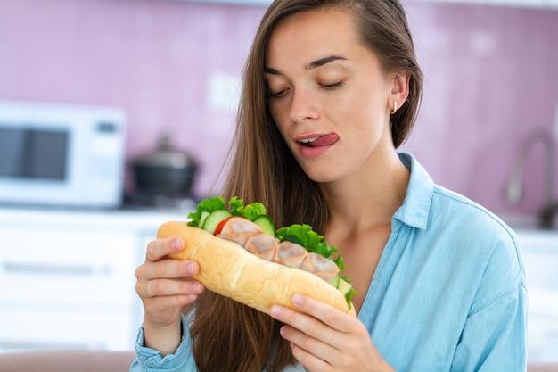 La donna affamata di cibo mangia il panino casalingo Foto Premium