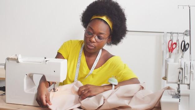 La donna afroamericana sveglia che usando una macchina per cucire cuce i vestiti Foto Premium