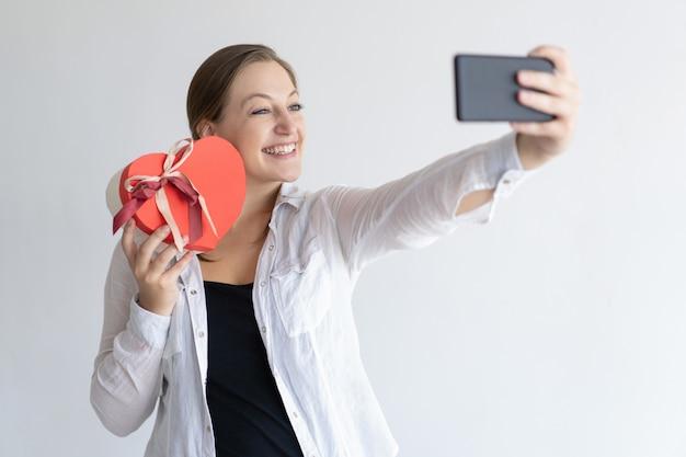 La donna allegra che prende la foto del selfie con il cuore ha modellato il contenitore di regalo Foto Gratuite