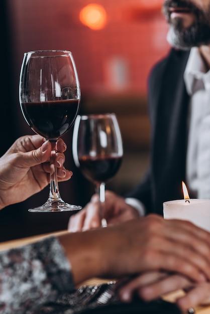 La donna alza un bicchiere e tiene per mano l'uomo amato Foto Premium
