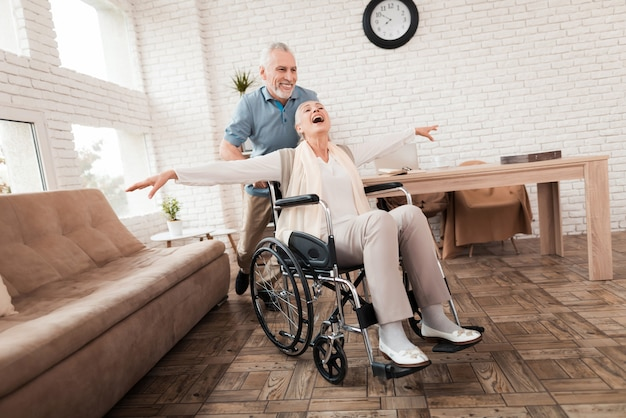 La donna anziana si prende cura dell'uomo senior in sedia a rotelle. Foto Premium