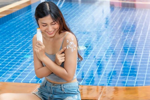 La donna asiatica attraente che tiene una bottiglia di crema solare e che applica la protezione solare a forma di sole uv protegge alla spalla. Foto Premium