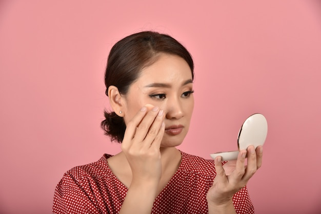 La donna asiatica che esamina il suo problema facciale nello specchio, la sensazione femminile infastidita dal suo aspetto riflesso mostra i segni dell'invecchiamento della pelle, problema della pelle della copertura di trucco. Foto Premium