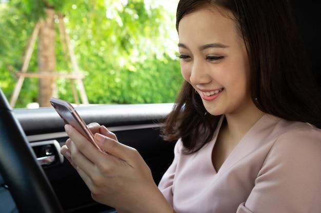 La donna asiatica che utilizza il telefono cellulare e gode di messaggi con il gruppo di amici dopo aver viaggiato durante l'ultima vacanza nella sua auto Foto Premium
