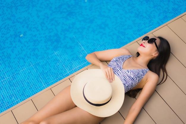 La donna asiatica del bello ritratto si rilassa il sorriso felice intorno alla piscina all'aperto Foto Gratuite