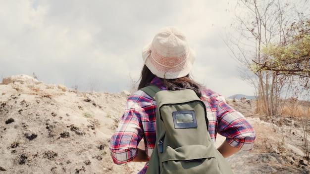La donna asiatica del viaggiatore con zaino e sacco a pelo della viandante che cammina alla cima della montagna, femminile gode delle sue feste sull'avventura di avventura che ritiene la libertà. Foto Gratuite