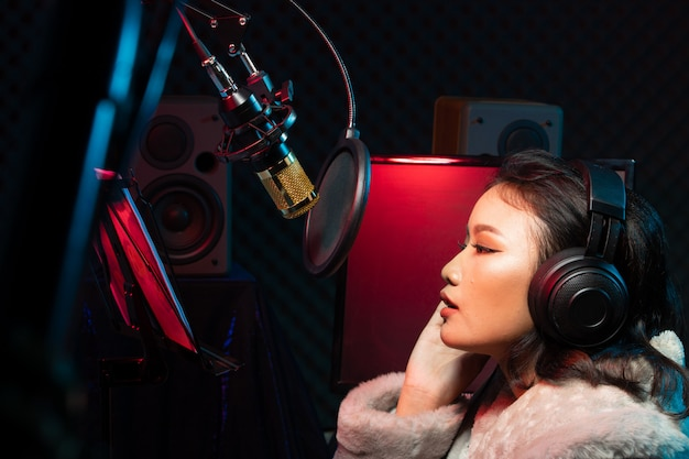 La donna asiatica dell'adolescente canta ad alta voce il suono di potere della canzone Foto Premium