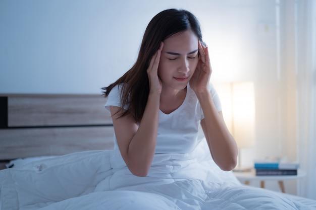 La donna asiatica ha un mal di testa può essere emicrania al mattino sul letto Foto Premium