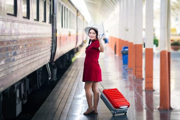 La donna asiatica incinta in vestito rosso che tiene una mappa e consegna su ciao dice con la valigia rossa in ferrovia Foto Premium