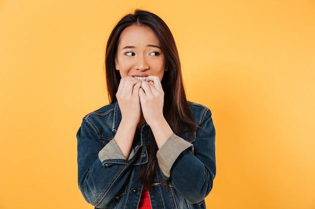 La donna asiatica preoccupata in rivestimento morde le dita e distogliere lo sguardo Foto Gratuite