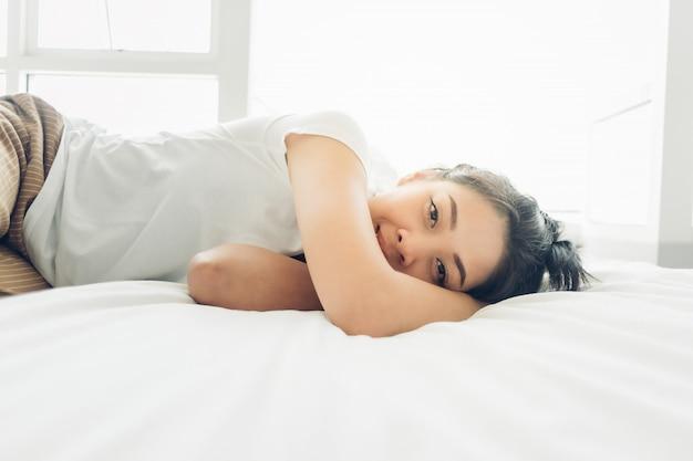 La donna asiatica sta dormendo sul suo letto accogliente bianco. Foto Premium