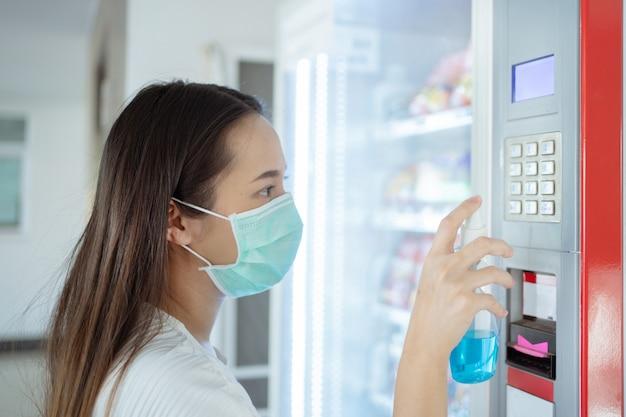 La donna asiatica sta iniettando alcol per uccidere i germi sul pulsante dei distributori automatici di bevande Foto Premium
