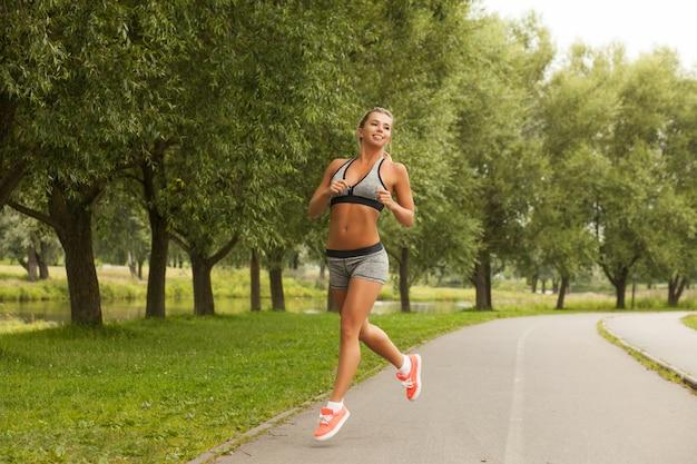 La donna bionda di bella forma fisica in buona salute nello sport di modo indossa il funzionamento e pratica l'yoga nel parco al tramonto Foto Premium