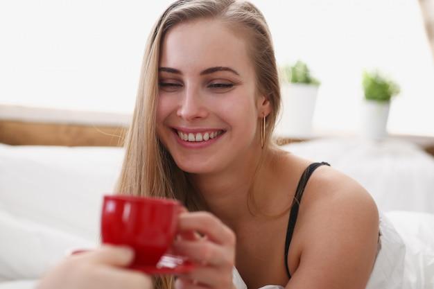 La donna bionda ha una tazza di tè e caffè al mattino presto nel suo letto Foto Premium
