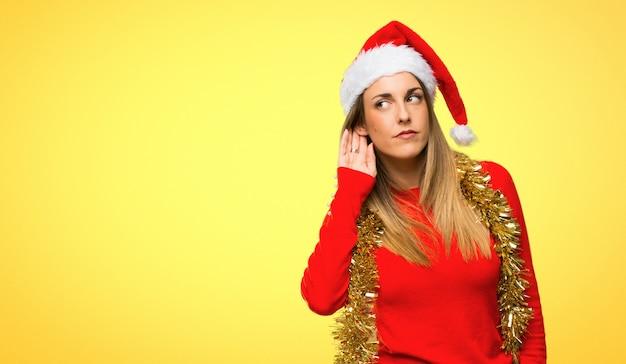 La donna bionda si è agghindata per le feste di natale che ascolta qualcosa Foto Premium