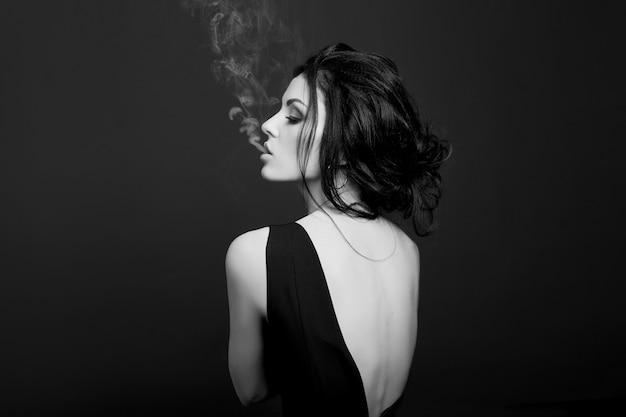 La donna castana dei cosmetici di trucco di bellezza di modo fuma su fondo scuro in vestito nero, fumo bianco dalla sua bocca. ragazze erotiche, in bianco e nero Foto Premium
