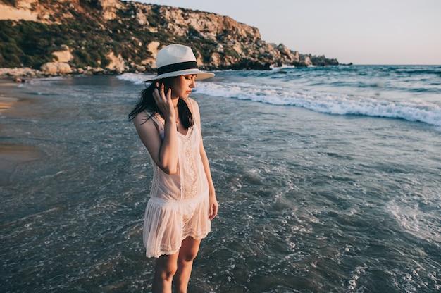 La donna caucasica cammina lungo la bella spiaggia Foto Premium