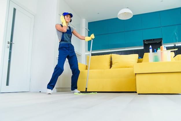 La donna caucasica come un pulitore professionale in cuffie che pulisce il pavimento con la zazzera ed ascolta la musica a casa. Foto Premium