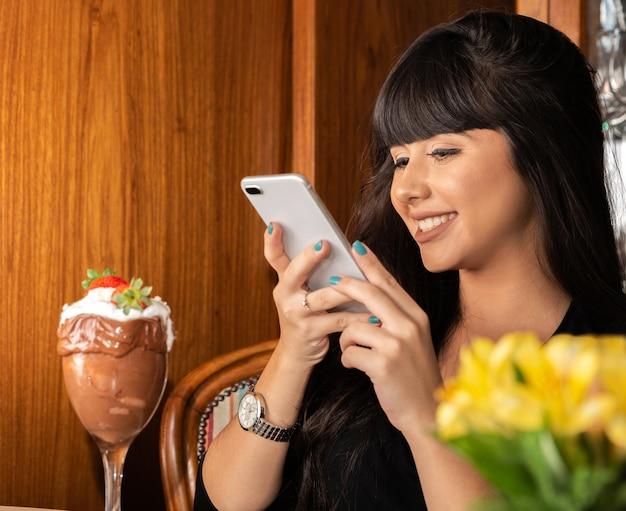 La donna che cattura le maschere di bianco delizioso del gelato mescola la fragola con uno smart phone. Foto Premium