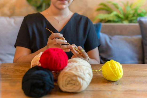 La donna che lavora a mano lavora all'uncinetto a casa come hobby. Foto Premium