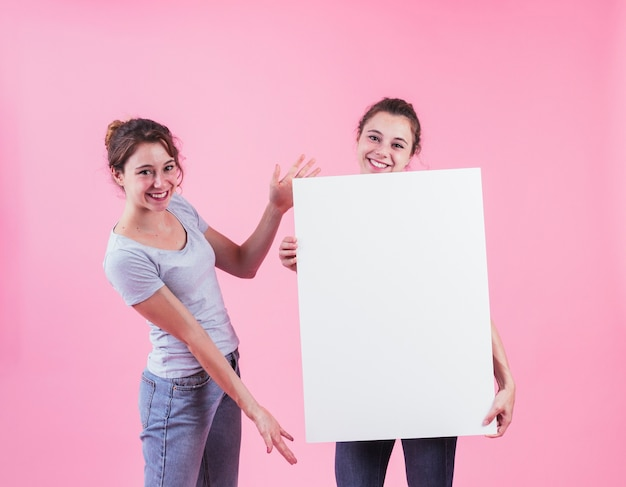 La donna che presenta il cartello in bianco tiene dal suo amico contro fondo rosa Foto Gratuite