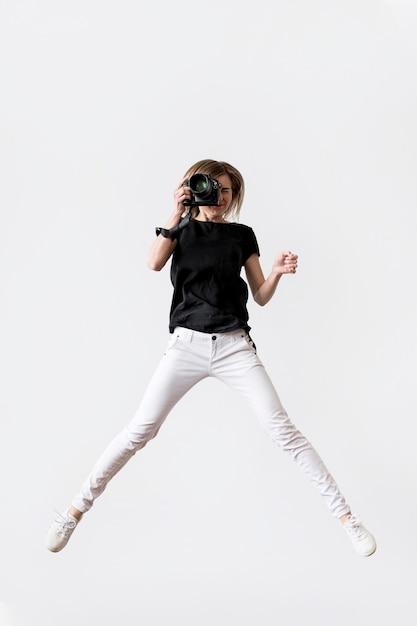 La donna che salta e che prende una foto Foto Gratuite