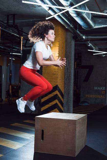 La donna che salta sulla scatola di legno nel fitness club Foto Gratuite