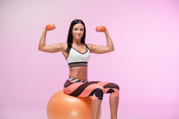 La donna che si allena contro lo studio rosa Foto Gratuite